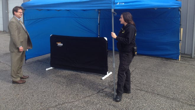 """Indianapolis Metropolitan Police Department Sgt. Mark Prater (left), a homicide detective, and Christine Ondek, a crime-scene technical leader with the city's Forensic Services Agency, show a tent and """"screen"""" purchased recently to help shield crime scenes from gawkers."""
