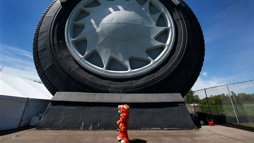 The Uniroyal Tire tiger mascot walks by the Giant Uniroyal Tire in Allen Park, Wednesday, May 20, 2015. The 80-foot-high, 12-ton tire is turning 50 and has stood alongside Interstate 94, near Detroit, since 1965, a year after it debuted at the New York World's Fair.