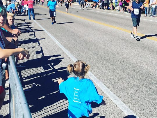Emmeline Orton,3, runs to her father Taylor Orton at the end of a marathon he planned to run with his wife.