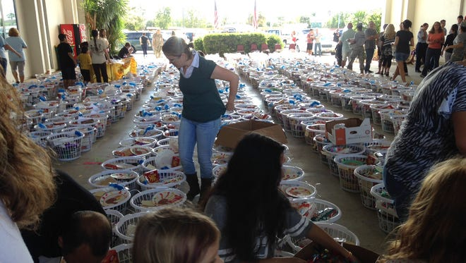 Volunteers for the Space Coast Basket Brigade fill laundry baskets with food for Thanksgiving,  bound for needy Brevard families.