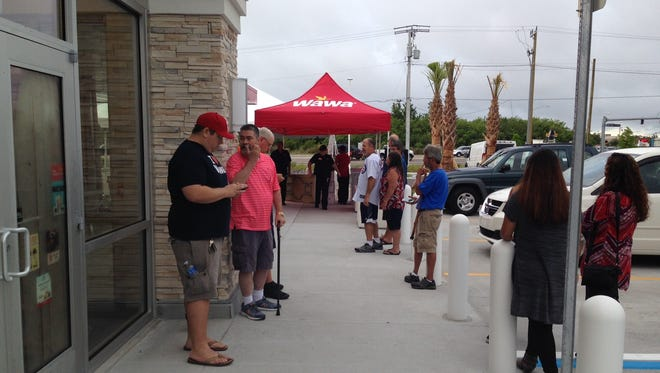 People lined up outside Wawa in Palm Shores Thursday morning ahead of the store's grand opening.