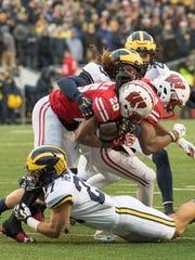 Michigan's Joe Hewlett (bottom) makes the tackle against Wisconsin.