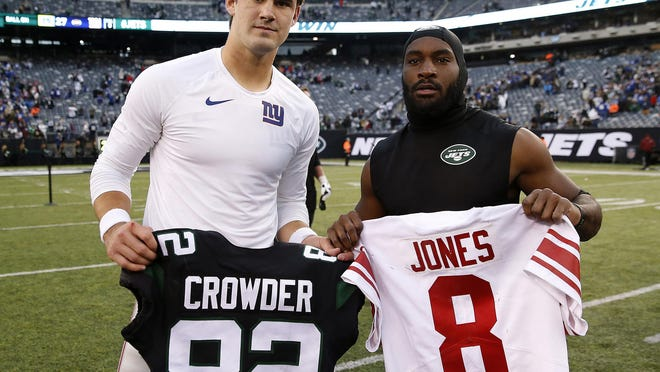 New York Giants quarterback Daniel Jones, left, and New York Jets wide receiver Jamison Crowder exchange jerseys after a game at MetLife Stadium in East Rutherford, New Jersey, on November 10, 2019.