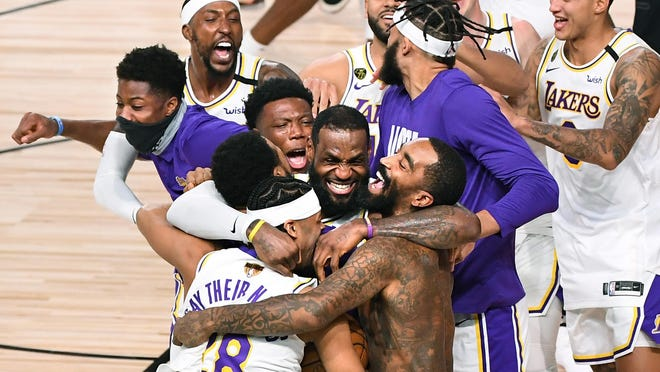 Los Angeles Lakers players, including LeBron James, center, celebrate the NBA Championship after defeating the Miami Heat in Game 6 of the NBA Finals on Sunday, Oct. 11, 2020 in Orlando, Fla.  [WALLY SKALIJ/LOS ANGELES TIMES/TNS}