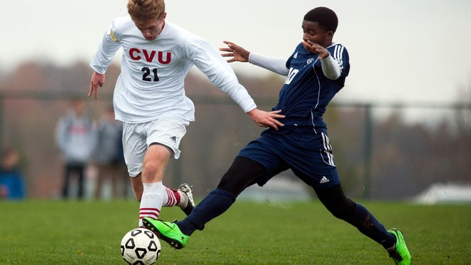 Burlington's Peter Makuni (10) battles for the ball with CVU's Patrick McCue (21) during the boys soccer playoff game between the Burlington Sea Horses and the Champlain Valley Union Redhawks at CVU High School on Wednesday afternoon October 22, 2014 in Hinesburg, Vermont. (BRIAN JENKINS, for the Free Press)