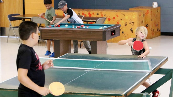 Evans Boys & Girls Club members Conner Martin, 10, left, and Jarid Cecil, 9, play a game of ping-pong while Lucus Rodriguez, 8, back left, and Austin Elkins, 9 work on their cue skills, Thursday, July 2, 2020, during an activitiy hour at the southside club.