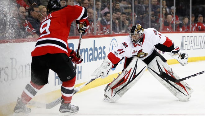 Senators goalie Craig Anderson leaves the crease to defend against Devils left wing Taylor Hall (9) during the second period of Tuesday night's game in Newark. Anderson made several big saves as Ottawa beat the Devils, 2-1.