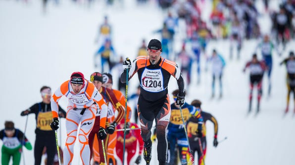 Men's and women's elite classic-style skiers start