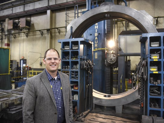 In this 2016 file photo, Bryan Burns stands next to a large valve in the manufacturing process at DeZURIK in Sartell.