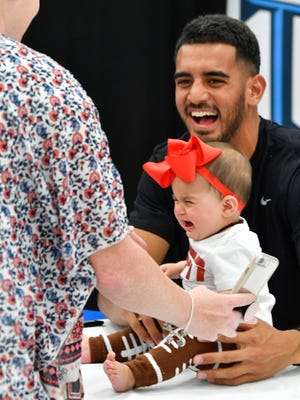Titans QB Marcus Mariota laughs as six-month-old Liliah Vazquez, dressed as a football, cries as she meet the Titan  at Fort Campbell as part of Titans Caravan Promotional tour.Monday April 30, 2018, in Ft. Campbell, KY.