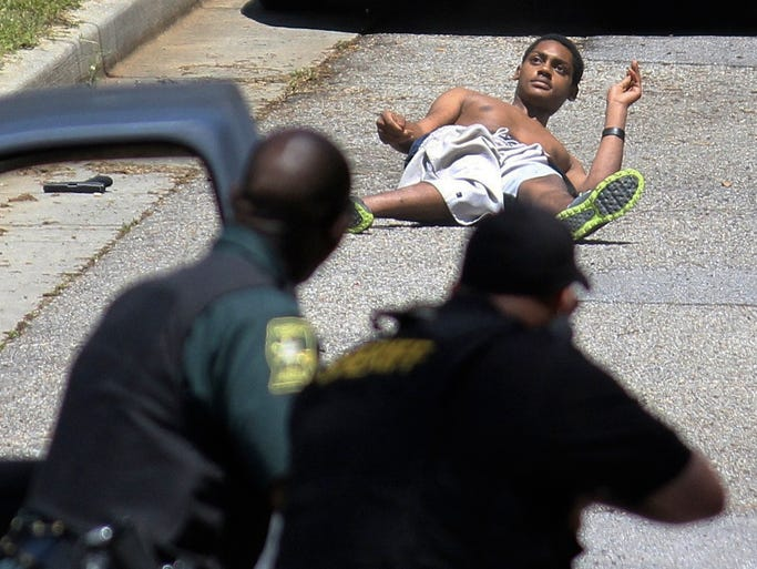 Emmanuel Wooten tries to get up after being shot in a standoff with Lauderdale County Sheriff's Department personnel in Meridian, Miss. on Friday, April 25, 2014 as his gun lies nearby, left. Wooten ran outside the house where he was holed up, opened fire and was shot by authorities. He died at a local hospital. Officials say Wooten was allegedly involved in a shootout with police two nights earlier. He was being sought for questioning in a break-in and shooting of a young girl and her mother in Marion. The girl is recovering from her wound. (AP Photo/The Meridan Star, Brian Livingston)