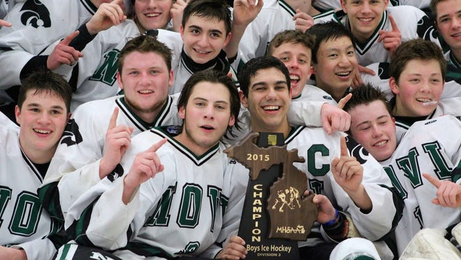Novi players celebrate with the Division 2 regional boys hockey trophy after beating Saline, 4-2, Saturday at Novi Ice Arena.