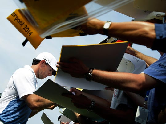 Rory McIlroy, of Northern Ireland, signs autographs after a practice round for the PGA Championship golf tournament at Valhalla Golf Club on Wednesday, Aug. 6, 2014, in Louisville, Ky. The tournament is set to begin on Thursday. (AP Photo/John Locher)