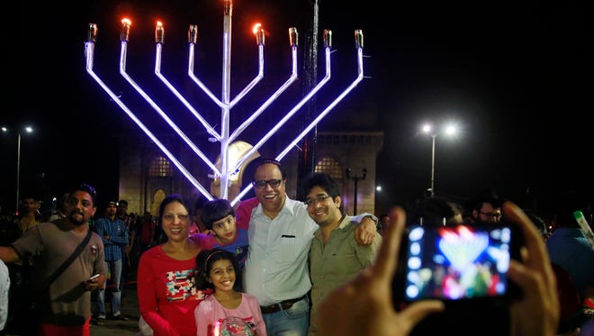 In this Dec. 13, 2015, photo, members of India's Jewish community pose for photographs after representatives of Mumbai's Chabad-Lubavitch ignited a menorah erected at the Gateway of India landmark as part of the Hanukkah celebration on the eighth and final night of the Jewish community's festival, in Mumbai, India. The Chabad-Lubavitch organization plans public menorah lightings in hundreds of cities around the world this year on Hanukkah, which begins the night of Dec. 24, 2016.