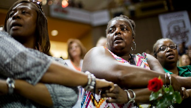 """Barbara Lloyd, of Charleston, S.C., cries as she joins hands with mourners during the singing of """"We Shall Overcome"""" at a memorial service for the victims of the shooting at Emanuel AME Church, Friday, June 19, 2015, in Charleston, S.C. (AP Photo/David Goldman)"""