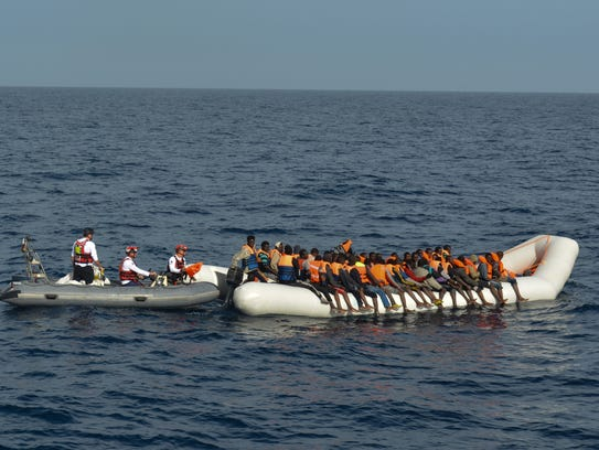 A crowded rubber boat floats on the Mediterranean Sea