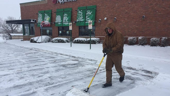 Nick Nordell of Liggett Construction shovels snow at Applebee's in Great Falls on Tuesday morning.