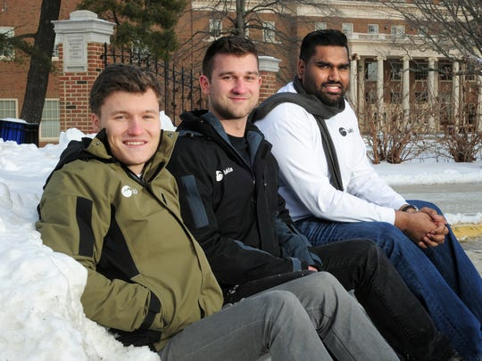 Lukla co-founders Massimiliano Squire, Michael Markesbery and Rithvik Venna sit in a snow bank outside the Farmer School of Business at Miami University in Oxford to demonstrate the jackets they've created.