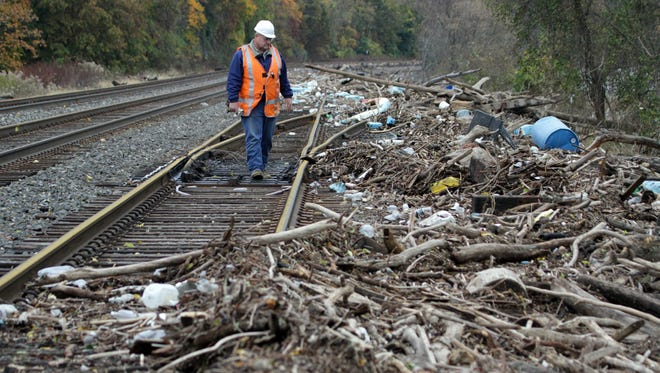 Tony Balassone, a track supervisor for Metro-North,  checks the tracks in Cortlandt Oct. 31, 2012 that are covered in debris washed up from the high winds and water surge from Superstorm Sandy. The track Balassone is walking is the westernmost one and is primarily used for freight.  ( Joe Larese/The Journal News )