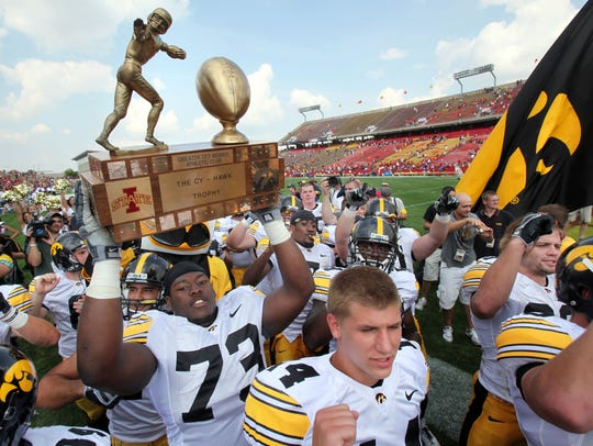 Iowa offensive lineman Adam Gettis (73) carries the Cy-Hawk Trophy off the Jack Trice Stadium field following the Hawkeyes' 35-3 win over Iowa State on Saturday, Sept. 12, 2009.