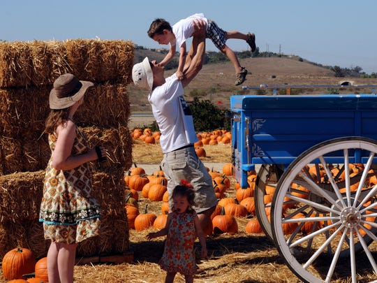 "A family is seen at the Fall Harvest Festival in 2016 at Underwood Family Farms in Moorpark. Areas of the farm were turned into an Iowa fair for the HBO show ""Veep."""