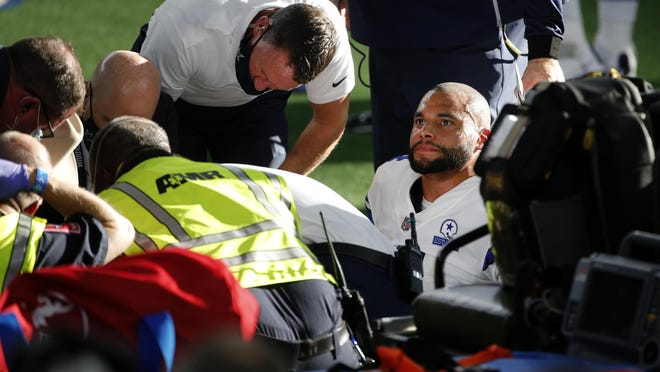 Dallas Cowboys quarterback Dak Prescott, right, looks off as first responders and team medical personnel assist Prescott after he suffered a lower right leg injury running the ball against the New York Giants in the second half of an NFL football game in Arlington, Texas, Sunday, Oct. 11, 2020.