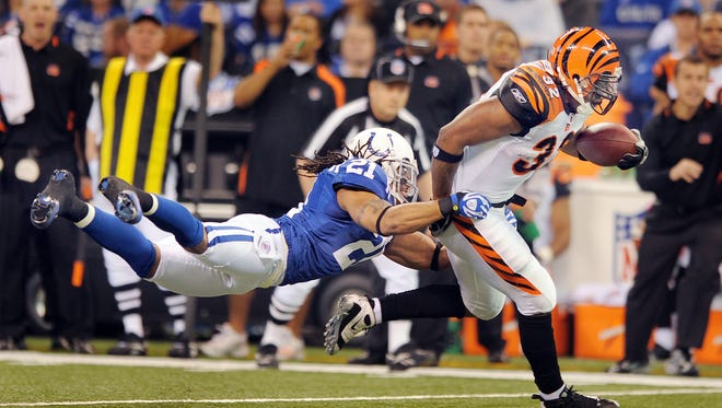 Indianapolis Colts Bob Sanders flies through the air to tackle the Bengals Cedric Benson (#32),right, in the first quarter of their game  Sunday afternoon at Lucas Oil Stadium.