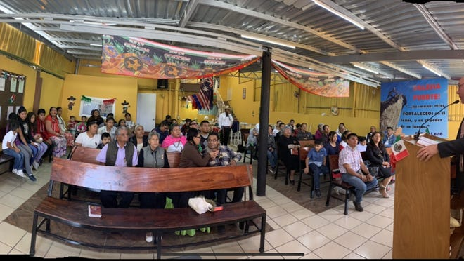 Mike Wallace (far right) delivers a sermon inside Hope Baptist Church, which is located in Mexico City. He and his wife, Mary, are missionaries who live about five minutes from the church.