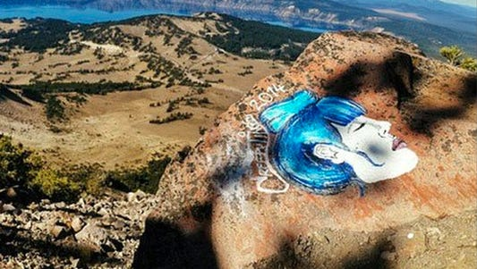 An undated photo taken from an Instagram posting shows an overlook of Crater Lake in Oregon with a rock painting.