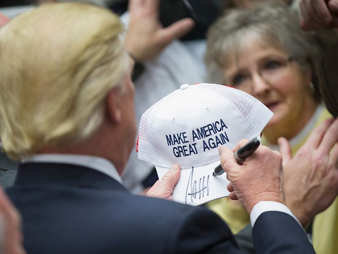 Donald Trump signs an autograph for a guest at a rally.