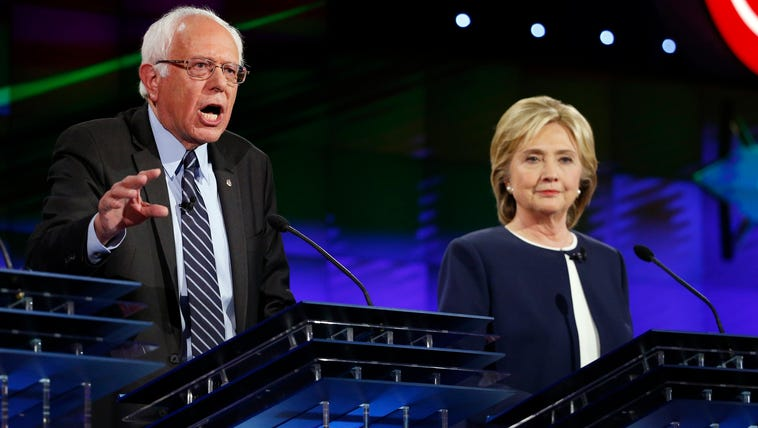 Hillary Clinton and Bernie Sanders participate in the