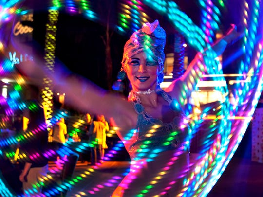 A performer twirls a neon hula hoop at the Cocktail