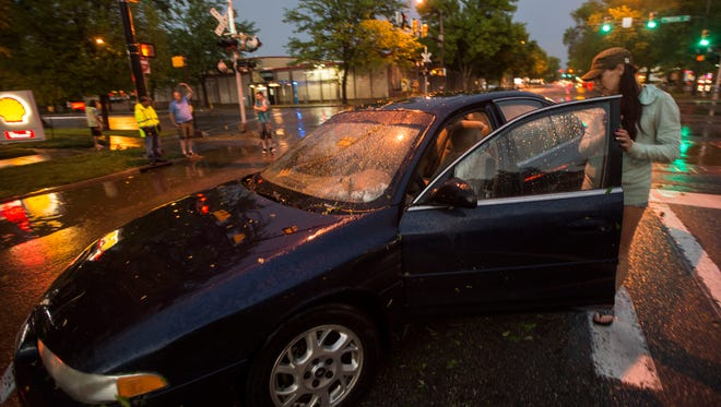Katie Leech shows the flood damage of her car on Tuesday, May 22, 2018, at Mulberry and Mason Street in Fort Collins, Colo. The car was flooded up past the floorboards and is waiting to be towed away.