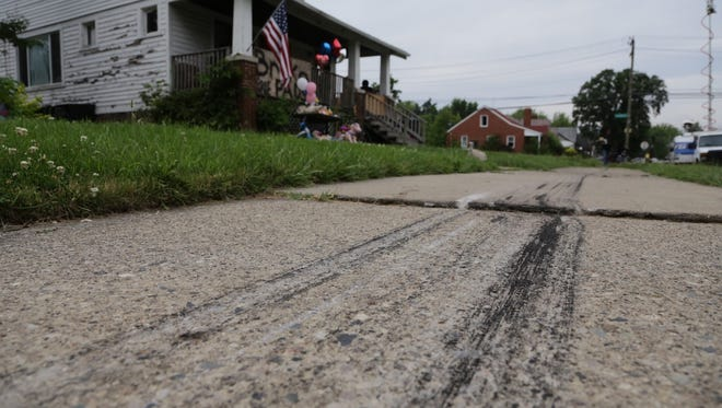 Tire marks are seen on Thursday June 25, 2015 stretching across the sidewalk where Makiah Jackson, 3, and Michaelangelo Jackson, 6, were hit while playing outside of their house during a high speed chase Wednesday evening near the corner of Frankfort and Nottingham in Detroit's east side.