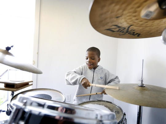 John Scarborough, 8, of Elmira, jams on a drum kit under the direction of Eric Doud at Knapp's School of Music. Scarborough has been a student a the studio for more than three months.