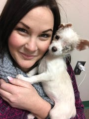 Sally Nail with the Humane Society of Southwest Missouri snuggles with Tinker, a puppy who was attacked by a larger dog last week.
