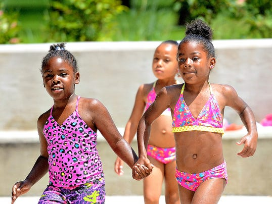 Cousins T'oni Mack, 6, left, Za'mya Smith, 6, right, and Jazale Williams, 6, center, head toward the water to cool off at Penn Park in York, Pa. on Wednesday, July 22, 2015. Dawn J. Sagert - dsagert@yorkdispatch.com