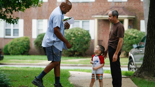 Mail carrier Vandrick R. Hamlin Sr. hands out candy to children as he travels his route around Lancaster Court Apartments on Wednesday. Hamlin, a 25-year US Postal Service employee, is organizing a back-to-school drive for children in need.