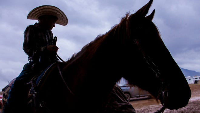 Trulin Johnston, 9, rides his families horse Peanut in the rain during the roping competition at the Welcome Home Ranch in Gilbert, Ariz., Saturday Jan. 31, 2015.