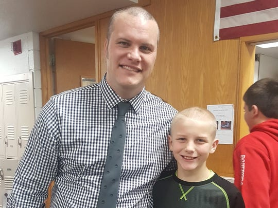 Pekin Middle School principal Tim Hadley poses with student Jackson Johnston after Hadley had the sixth-grader shave his head Tuesday, Jan. 10, 2017.