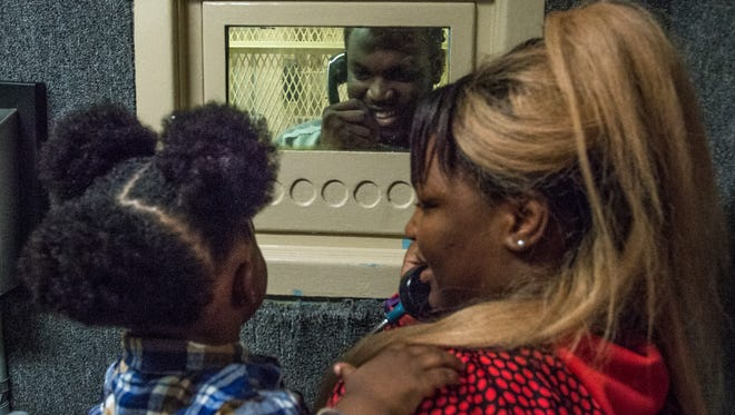 Dvonte Lockley, an inmate at the Montgomery Municipal Jail, smiles and waves from behind a glass window as he talks with his son, Dvonte Lockley Jr., 1, and the child's mother, Laporchie Howard, on Sunday, Dec. 27, 2015. It was the first time he had been allowed to see his son in a month. For the first time, young children of inmates at the jail were allowed to come in and see their parents for a Christmas visit this past weekend. Normally, no one under age 18 is allowed to visit inmates.