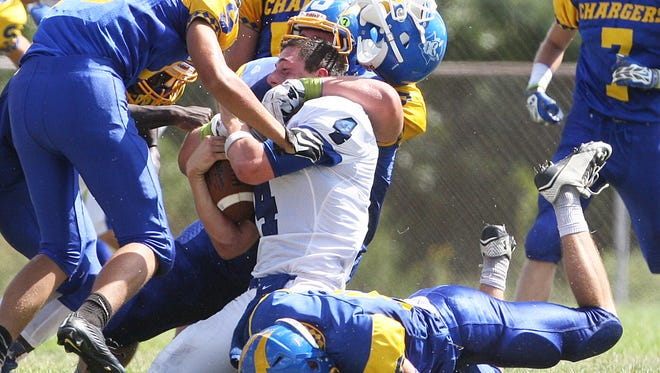 Action photos of Shore Regional at Spotswood football on Saturday September 19, 2015.Shore Regional quarterback # 4 (center)Matt Pennell has his helmet fly off as he is tackled by a host of Spotswood defenders.