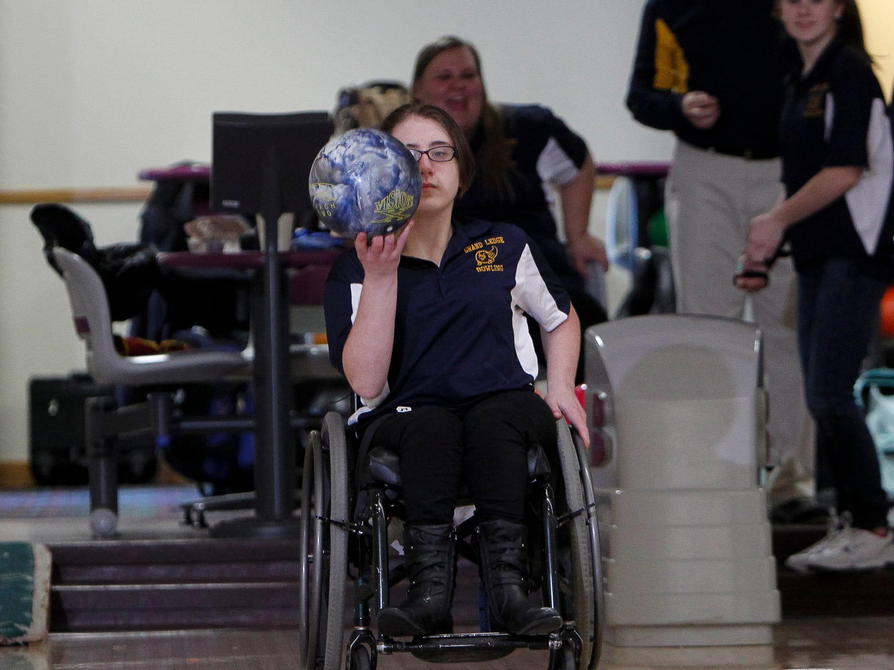 Grand Ledge Bowling team member, sophomore Caitlyn Wells sizes up the pins before sending the ball down the lane at Royal Scott Tuesday. Wells has spina bifida, and has been in a wheelchair her entire life.