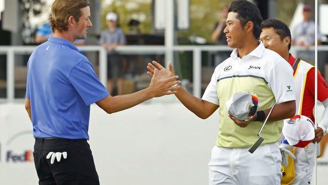 No hats here as Webb Simpson, left, congratulates Hideki Matsuyama following Matsuyama's playoff win in the Waste Management Phoenix Open on Sunday.