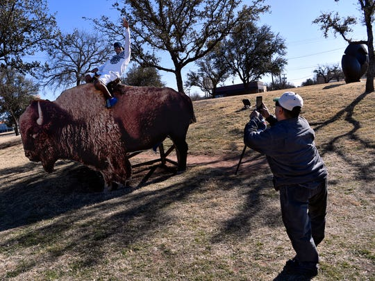 Henry Valadez takes a photograph of his friend Raymond McGaffeny atop the buffalo display in the railroad right of way. Planting trees to beautify the right of way was one of the first projects of the Dodge Jones Foundation.