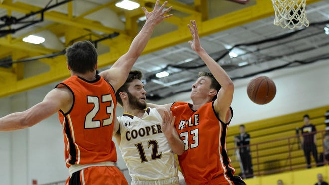 Cooper's Chris McNeil (12) collects a trip to the free throw line as he is fouled in traffic by Ryle's Zach Benton (33), Dec. 12, 2017.