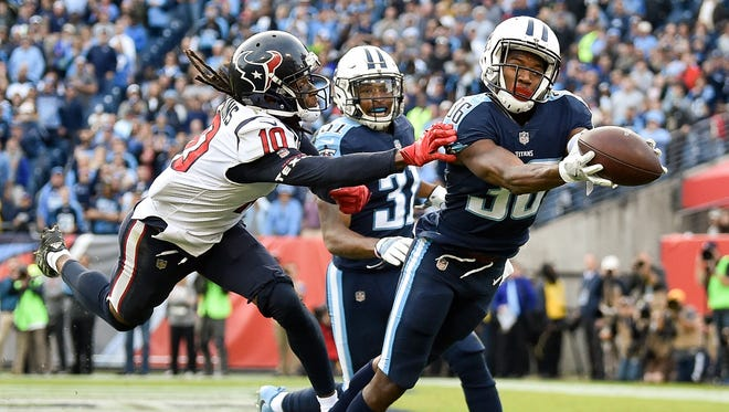 Titans cornerback LeShaun Sims (36) intercepts a pass intended for Texans wide receiver DeAndre Hopkins (10) during the second half Sunday.