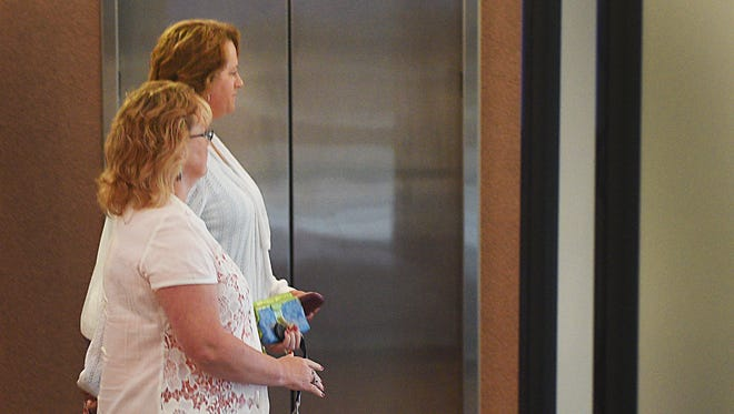 Stephanie Hubers, background, leaves the Minnehaha County Clerk-Courts Tuesday, June 26, in Sioux Falls.