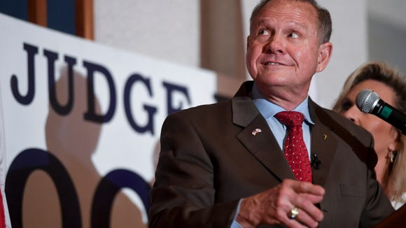 U.S. Senate candidate Roy Moore glances up at the big