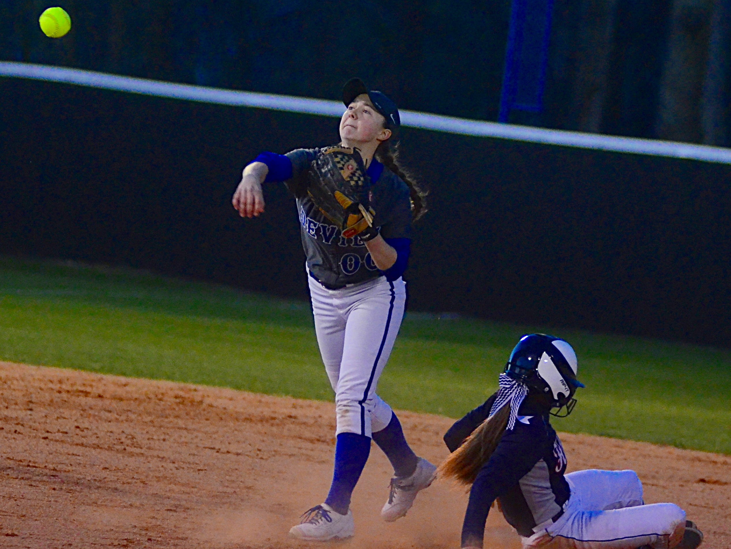 White House High freshman second baseman Grace Fillmore attempts to turn a double play as White House Heritage's Alex Martin slides into second base.